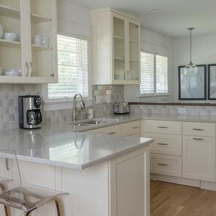 インディアナポリスの中サイズのエクレクティックスタイルのおしゃれなキッチン (アンダーカウンターシンク、ガラス扉のキャビネット、白いキャビネット、グレーのキッチンパネル、サブウェイタイルのキッチンパネル、シルバーの調理設備の、無垢フローリング、黄色い床、グレーのキッチンカウンター) の写真