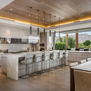 Trendy l-shaped gray floor kitchen photo in Other with flat-panel cabinets, gray cabinets, paneled appliances and an island