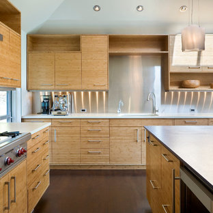 Trendy kitchen photo in Seattle with flat-panel cabinets, light wood cabinets, metallic backsplash, an undermount sink, solid surface countertops and stainless steel appliances