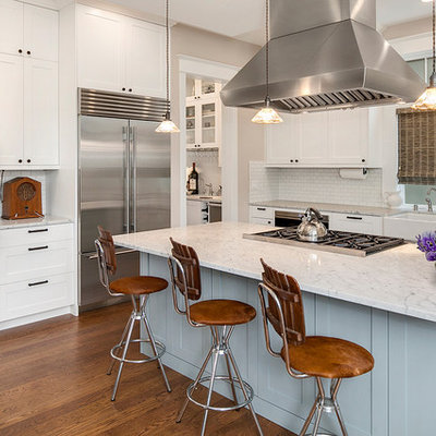Country medium tone wood floor kitchen photo in Seattle with a farmhouse sink, shaker cabinets, white cabinets, marble countertops, white backsplash, subway tile backsplash, stainless steel appliances and an island