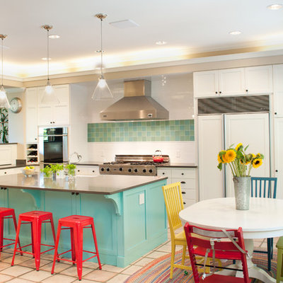 Eat-in kitchen - large modern u-shaped terra-cotta tile and beige floor eat-in kitchen idea in Seattle with white cabinets, stainless steel appliances, a farmhouse sink, raised-panel cabinets, solid surface countertops, white backsplash, subway tile backsplash and an island