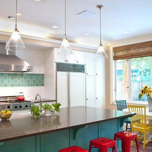 Inspiration for a large modern u-shaped terra-cotta floor and beige floor eat-in kitchen remodel in Seattle with a farmhouse sink, raised-panel cabinets, white cabinets, solid surface countertops, white backsplash, subway tile backsplash, stainless steel appliances and an island