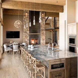 Cette image montre une grand cuisine américaine parallèle chalet avec des portes de placard en bois clair, un îlot central, un évier encastré, un placard à porte shaker, un électroménager en acier inoxydable, un sol beige, un plan de travail en quartz et un sol en bois brun.