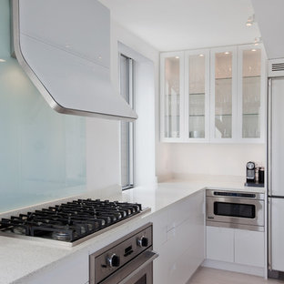 Example of a minimalist kitchen design in New York with glass-front cabinets and white cabinets