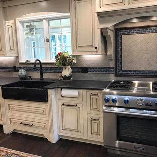 Lantlig inredning av ett mellanstort kök, med en rustik diskho, skåp i slitet trä, rostfria vitvaror, luckor med upphöjd panel, bänkskiva i täljsten, grått stänkskydd, stänkskydd i keramik, mörkt trägolv, en köksö och brunt golv