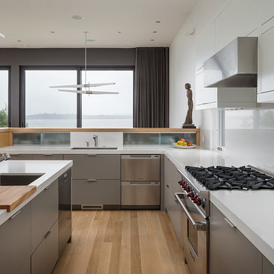 Inspiration for a mid-sized modern u-shaped light wood floor eat-in kitchen remodel in Seattle with an undermount sink, flat-panel cabinets, gray cabinets, stainless steel appliances, quartz countertops, white backsplash and an island