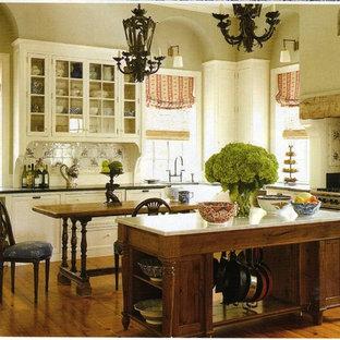 Foto de cocina en L, clásica, extra grande, abierta, con armarios tipo vitrina, puertas de armario blancas, encimera de granito, suelo de madera clara y una isla