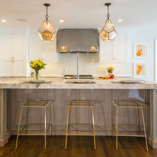 Huge transitional eat-in kitchen pictures - Eat-in kitchen - huge transitional l-shaped medium tone wood floor and brown floor eat-in kitchen idea in New York with a farmhouse sink, beaded inset cabinets, white cabinets, quartzite countertops, white backsplash, porcelain backsplash, stainless steel appliances, an island and gray countertops