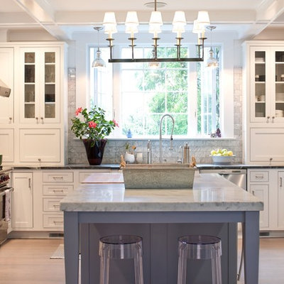 Example of a mid-sized classic u-shaped light wood floor enclosed kitchen design in New York with beaded inset cabinets, stainless steel appliances, white cabinets, white backsplash, stone tile backsplash, marble countertops and an island