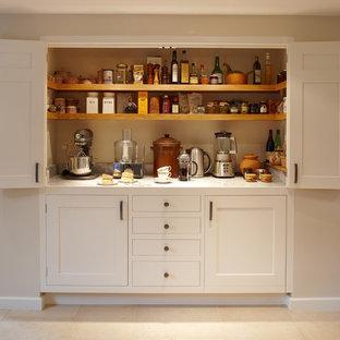 На фото: большая кухня в классическом стиле с кладовкой, фасадами в стиле шейкер, белыми фасадами, мраморной столешницей и полом из известняка с