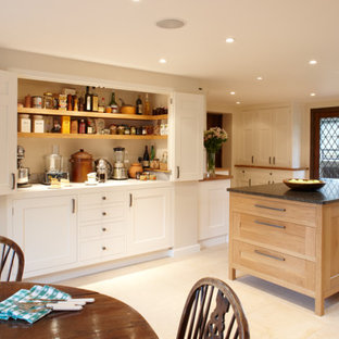 Photo of a large modern l-shaped eat-in kitchen in Surrey with shaker cabinets, light wood cabinets, granite benchtops, black splashback, stainless steel appliances, limestone floors and with island.