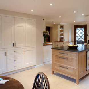 Design ideas for a large traditional l-shaped eat-in kitchen in Surrey with shaker cabinets, light wood cabinets, granite benchtops, black splashback, stainless steel appliances, limestone floors and with island.