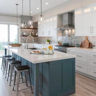 サンディエゴの大きいトランジショナルスタイルのおしゃれなキッチン (アンダーカウンターシンク、白いキャビネット、グレーのキッチンパネル、シルバーの調理設備の、淡色無垢フローリング、ベージュの床、白いキッチンカウンター、落し込みパネル扉のキャビネット、クオーツストーンカウンター、ガラスタイルのキッチンパネル) の写真