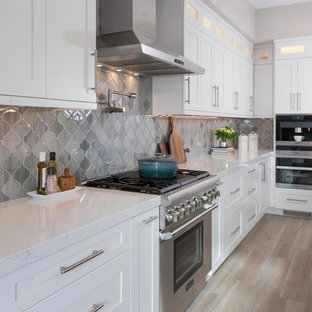 Large transitional kitchen in San Diego with an undermount sink, white cabinets, quartz benchtops, grey splashback, glass tile splashback, stainless steel appliances, light hardwood floors, with island, beige floor, white benchtop and shaker cabinets.