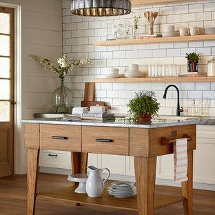 Lantlig inredning av ett kök, med en rustik diskho, släta luckor, vita skåp, bänkskiva i zink, vitt stänkskydd, stänkskydd i tunnelbanekakel, mellanmörkt trägolv och en köksö