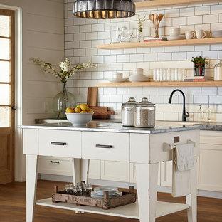 Exempel på ett lantligt kök, med en rustik diskho, släta luckor, vita skåp, bänkskiva i zink, vitt stänkskydd, stänkskydd i tunnelbanekakel, mellanmörkt trägolv och en köksö