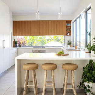 Photo of a tropical u-shaped kitchen in Sunshine Coast with an undermount sink, flat-panel cabinets, medium wood cabinets, window splashback, panelled appliances, a peninsula and beige floor.