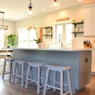 Mid-sized farmhouse eat-in kitchen ideas - Eat-in kitchen - mid-sized farmhouse l-shaped eat-in kitchen idea in New York with an undermount sink, shaker cabinets, white cabinets, quartz countertops, white backsplash, subway tile backsplash, black appliances, an island and white countertops