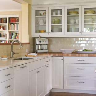 Traditional kitchen inspiration - Kitchen - traditional kitchen idea in Seattle with an undermount sink, shaker cabinets, white cabinets, wood countertops, beige backsplash and subway tile backsplash