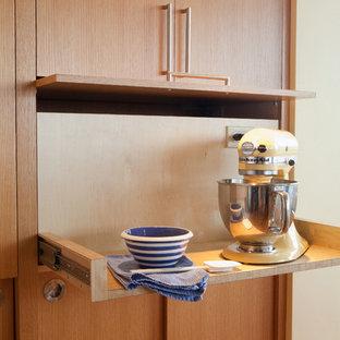 Bild på ett stort retro kök, med släta luckor, skåp i mellenmörkt trä, rostfria vitvaror, mellanmörkt trägolv och en köksö