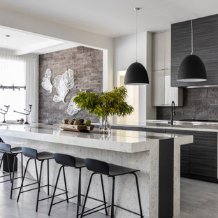 Design ideas for a contemporary kitchen in Houston with flat-panel cabinets, black splashback, with island, grey floor and multi-coloured benchtop.
