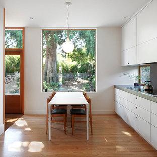 Mittelgroße Moderne Wohnküche in L-Form mit braunem Holzboden, flächenbündigen Schrankfronten, weißen Schränken, Edelstahl-Arbeitsplatte, Rückwand-Fenster und braunem Boden in Seattle