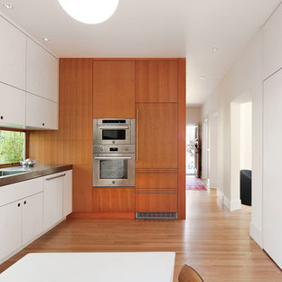 Kitchen - mid-sized contemporary l-shaped light wood floor and brown floor kitchen idea in Seattle with flat-panel cabinets, white cabinets, stainless steel appliances, an undermount sink, window backsplash and no island