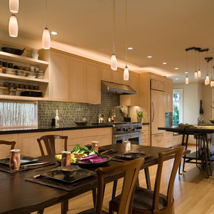 Mid-sized transitional galley eat-in kitchen in Seattle with an undermount sink, light wood cabinets, limestone benchtops, panelled appliances, light hardwood floors and with island.