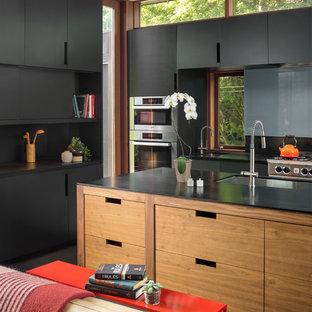 シアトルのコンテンポラリースタイルのおしゃれなキッチン (アンダーカウンターシンク、フラットパネル扉のキャビネット、黒いキャビネット、シルバーの調理設備、グレーの床) の写真