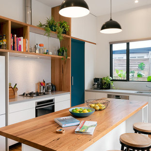 Design ideas for a mid-sized contemporary single-wall kitchen in Melbourne with an undermount sink, flat-panel cabinets, white cabinets, wood benchtops, white splashback, mosaic tile splashback, stainless steel appliances, medium hardwood floors, with island and grey benchtop.