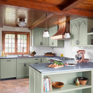 Photo of a mid-sized u-shaped kitchen in Seattle with an undermount sink, recessed-panel cabinets, green cabinets, white splashback, a peninsula, brown floor, grey benchtop, exposed beam, wood, marble benchtops and ceramic splashback.