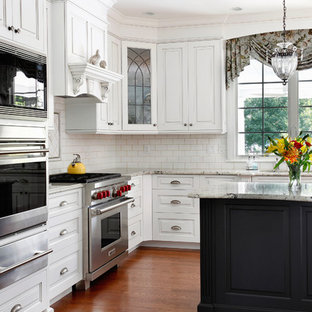 Eat-in kitchen - traditional l-shaped eat-in kitchen idea in Philadelphia with an undermount sink, raised-panel cabinets, white cabinets, granite countertops, white backsplash, subway tile backsplash and stainless steel appliances