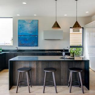 Foto de cocina en L, contemporánea, con armarios con paneles lisos, puertas de armario de madera en tonos medios, electrodomésticos de acero inoxidable, suelo de madera clara, una isla, fregadero bajoencimera y salpicadero blanco