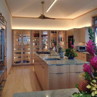 Geschlossene, Große Asiatische Küche in U-Form mit Einbauwaschbecken, Glasfronten, hellen Holzschränken, Granit-Arbeitsplatte, Küchenrückwand in Beige, Rückwand aus Marmor, Küchengeräten aus Edelstahl, Bambusparkett, Kücheninsel, beigem Boden und grüner Arbeitsplatte in Hawaii