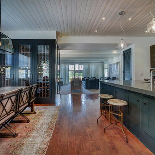 Offene, Zweizeilige Klassische Küche mit Schrankfronten im Shaker-Stil, schwarzen Schränken, Küchenrückwand in Weiß, braunem Holzboden, Kücheninsel und braunem Boden in Los Angeles