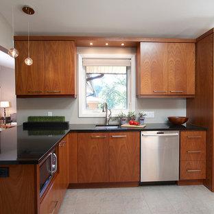 トロントの広いおしゃれなキッチン (ダブルシンク、フラットパネル扉のキャビネット、中間色木目調キャビネット、オニキスカウンター、セラミックタイルの床) の写真