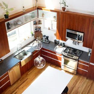 Foto de cocina en L, contemporánea, de tamaño medio, con despensa, fregadero sobremueble, armarios con paneles lisos, puertas de armario de madera oscura, encimera de granito, electrodomésticos de acero inoxidable, suelo de madera clara y una isla