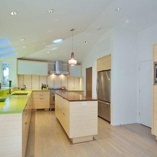 サンフランシスコの大きいコンテンポラリースタイルのおしゃれなキッチン (ドロップインシンク、フラットパネル扉のキャビネット、淡色木目調キャビネット、クオーツストーンカウンター、ベージュキッチンパネル、セラミックタイルのキッチンパネル、シルバーの調理設備の、淡色無垢フローリング、緑のキッチンカウンター) の写真
