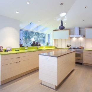 サンフランシスコの大きいコンテンポラリースタイルのおしゃれなキッチン (ドロップインシンク、クオーツストーンカウンター、緑のキッチンパネル、セラミックタイルのキッチンパネル、シルバーの調理設備の、淡色無垢フローリング、フラットパネル扉のキャビネット、淡色木目調キャビネット、緑のキッチンカウンター) の写真