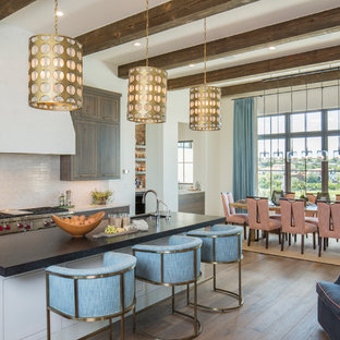 Inspiration for a classic galley kitchen/diner in Austin with a submerged sink, beaded cabinets, dark wood cabinets, beige splashback, matchstick tiled splashback, stainless steel appliances, medium hardwood flooring and an island.