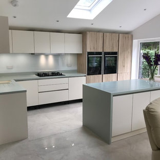 Mid-sized modern l-shaped eat-in kitchen in Kent with an undermount sink, flat-panel cabinets, white cabinets, solid surface benchtops, white splashback, glass sheet splashback, black appliances, porcelain floors, with island, grey floor and green benchtop.