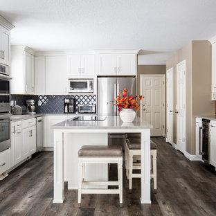 Diseño de cocina en L, tradicional renovada, de tamaño medio, con armarios estilo shaker, puertas de armario blancas, encimera de cuarzo compacto, salpicadero azul, electrodomésticos de acero inoxidable, suelo vinílico, una isla, suelo marrón, encimeras grises y salpicadero de azulejos de cerámica