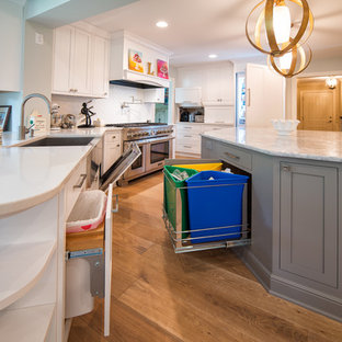 Large contemporary enclosed kitchen designs - Large trendy galley light wood floor enclosed kitchen photo in Minneapolis with a farmhouse sink, shaker cabinets, white cabinets, quartz countertops, white backsplash, glass tile backsplash, stainless steel appliances and an island