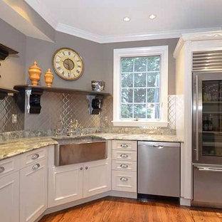 Idéer för avskilda, mellanstora funkis l-kök, med en rustik diskho, luckor med profilerade fronter, beige skåp, granitbänkskiva, stänkskydd med metallisk yta, rostfria vitvaror, mellanmörkt trägolv och en halv köksö