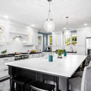 Large traditional l-shaped kitchen/diner in Philadelphia with a belfast sink, recessed-panel cabinets, white cabinets, soapstone worktops, white splashback, metro tiled splashback, stainless steel appliances, dark hardwood flooring and an island.
