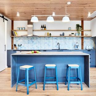 Cette image montre une cuisine américaine design en L de taille moyenne avec des portes de placard bleues, une crédence en carreau de céramique, un sol en bois clair, un îlot central, un sol beige, un évier posé, un placard à porte plane, une crédence bleue, un électroménager en acier inoxydable, un plan de travail bleu et un plafond en bois.