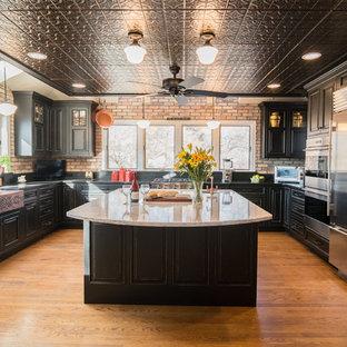 ボストンの大きいトランジショナルスタイルのおしゃれなキッチン (エプロンフロントシンク、インセット扉のキャビネット、ヴィンテージ仕上げキャビネット、御影石カウンター、赤いキッチンパネル、レンガのキッチンパネル、シルバーの調理設備の、無垢フローリング、茶色い床) の写真