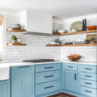 Idéer för mellanstora lantliga vitt kök, med skåp i shakerstil, blå skåp, vitt stänkskydd, stänkskydd i tegel, mellanmörkt trägolv, en rustik diskho och brunt golv
