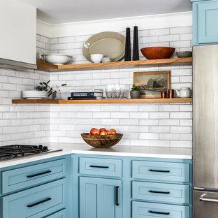 ポートランド(メイン)の中サイズのカントリー風おしゃれなキッチン (シェーカースタイル扉のキャビネット、青いキャビネット、白いキッチンパネル、レンガのキッチンパネル、シルバーの調理設備の、無垢フローリング、アイランドなし、赤い床、白いキッチンカウンター) の写真