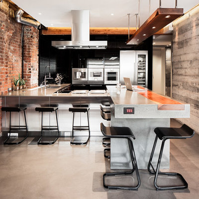 Example of a large urban u-shaped concrete floor open concept kitchen design in Vancouver with concrete countertops, stainless steel appliances, flat-panel cabinets, black backsplash, a peninsula and black cabinets